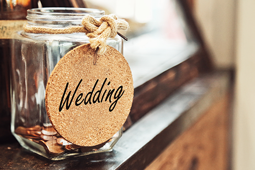 jar filled with coins and wedding sign on front